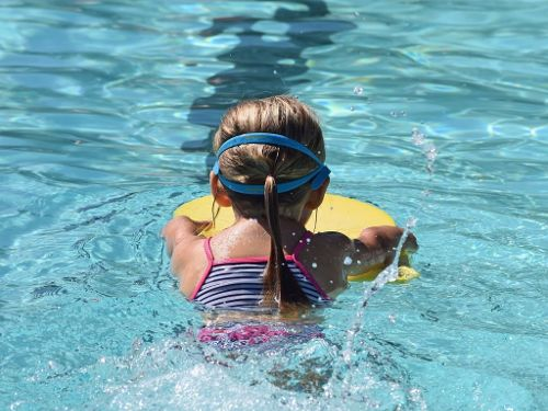 Young swimmer using kickboard